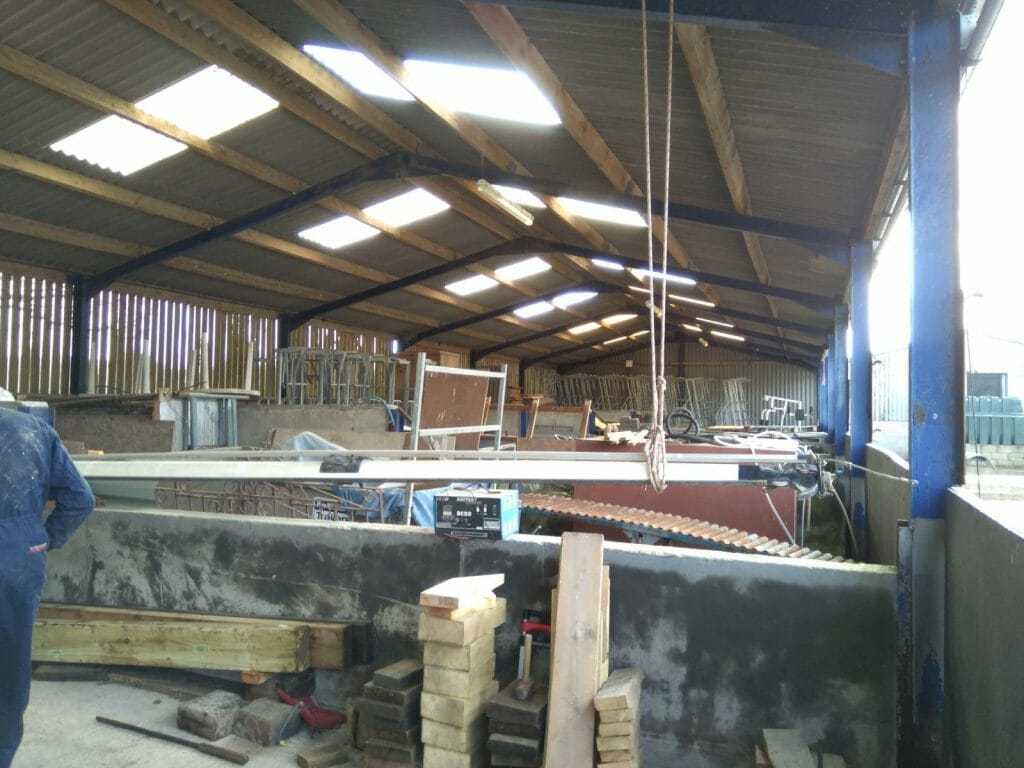 The mast now hanging from the roof to allow the oil drum it was resting on to be used in raising the boat.