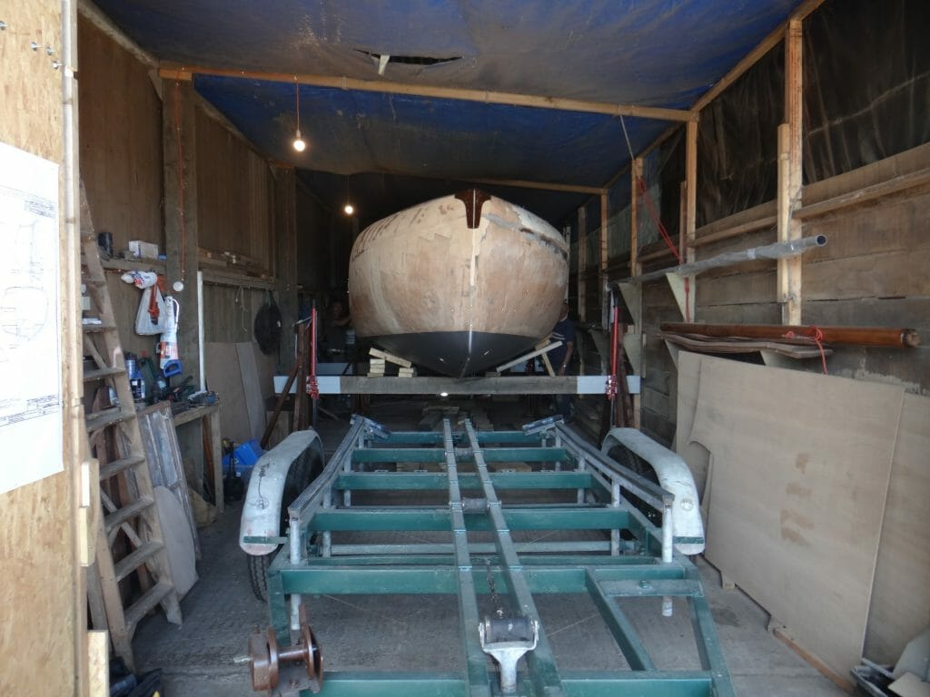 Aft and forward beams are raised with a person on each jack. the boat sits level and ready for the trailer to be wheeled into position.
