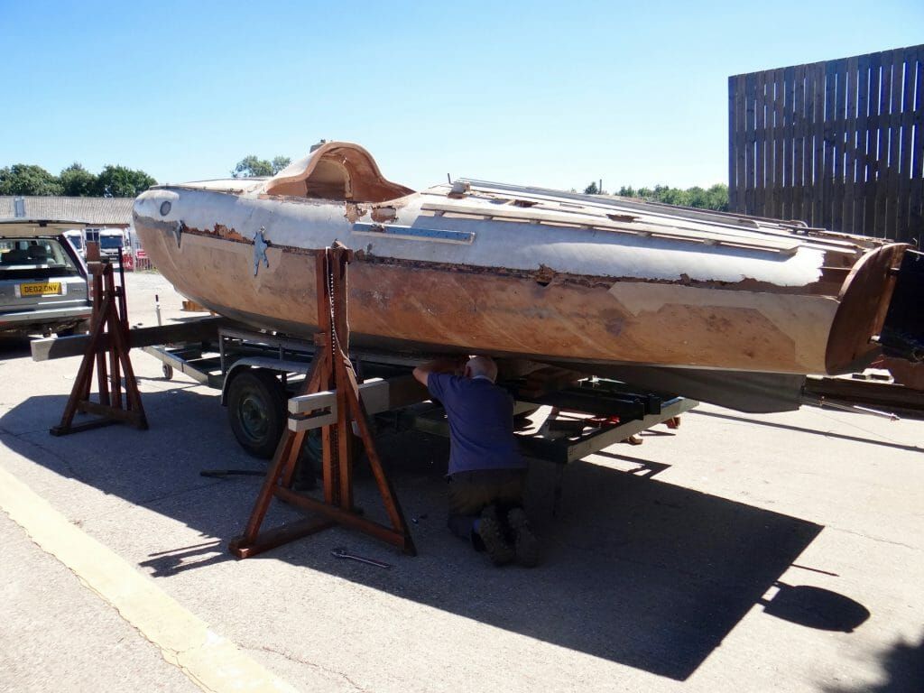 The lifting beams and jacks are called into play again to lower the boat fully onto the trailer.
