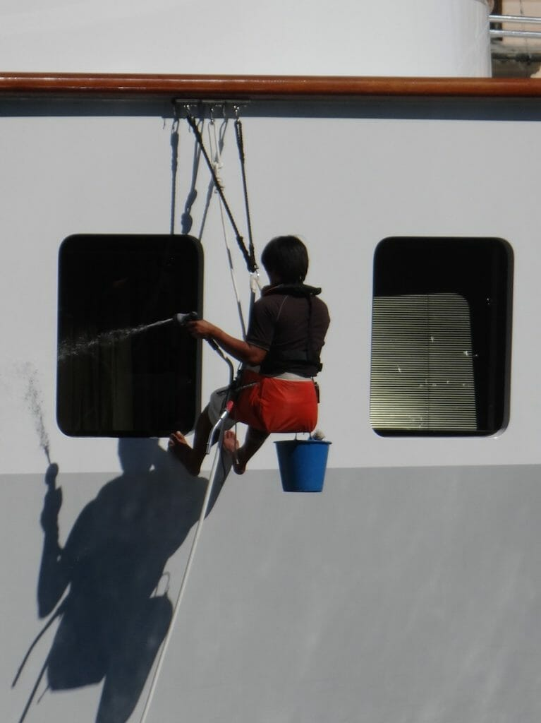 Every morning all of the windows were cleaned by a crew member hanging from a car running on track under the handrail. The full length of the boat.
