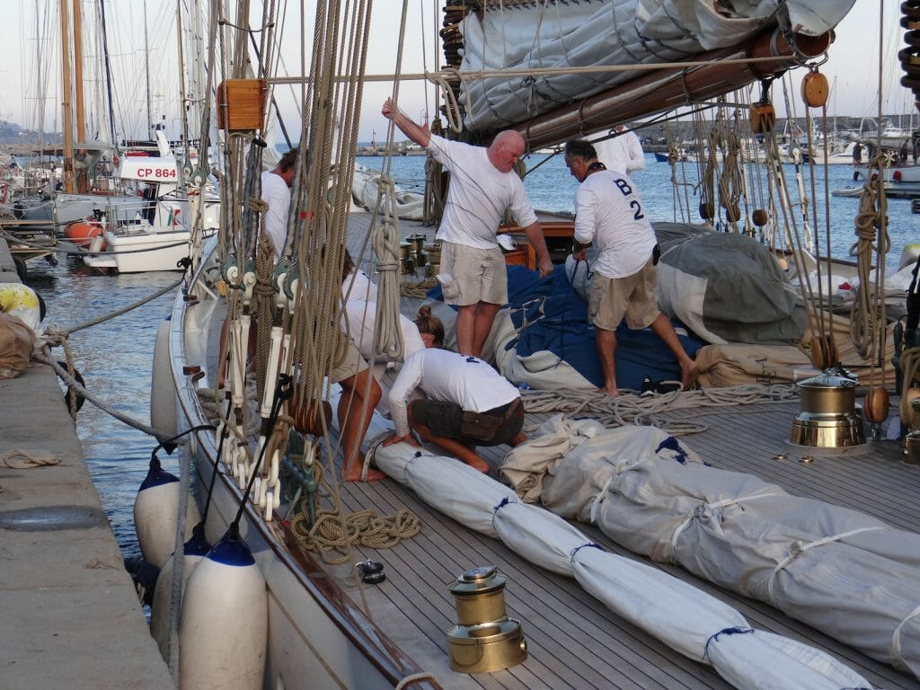 Preparing the topsail for hoisting next day.  There had been an issue during the afternoon - witness the man walking up the gaff in earlier photo.